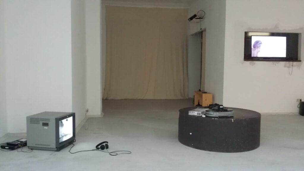 Auf dem Foto ist ein Ausstellungsraum mit verschiedenen Objekten zu sehen. Links steht ein Fernseher auf dem Boden, in der Mitte befindet sich ein Tisch und rechts steht noch ein Fernseher in einer Nische.