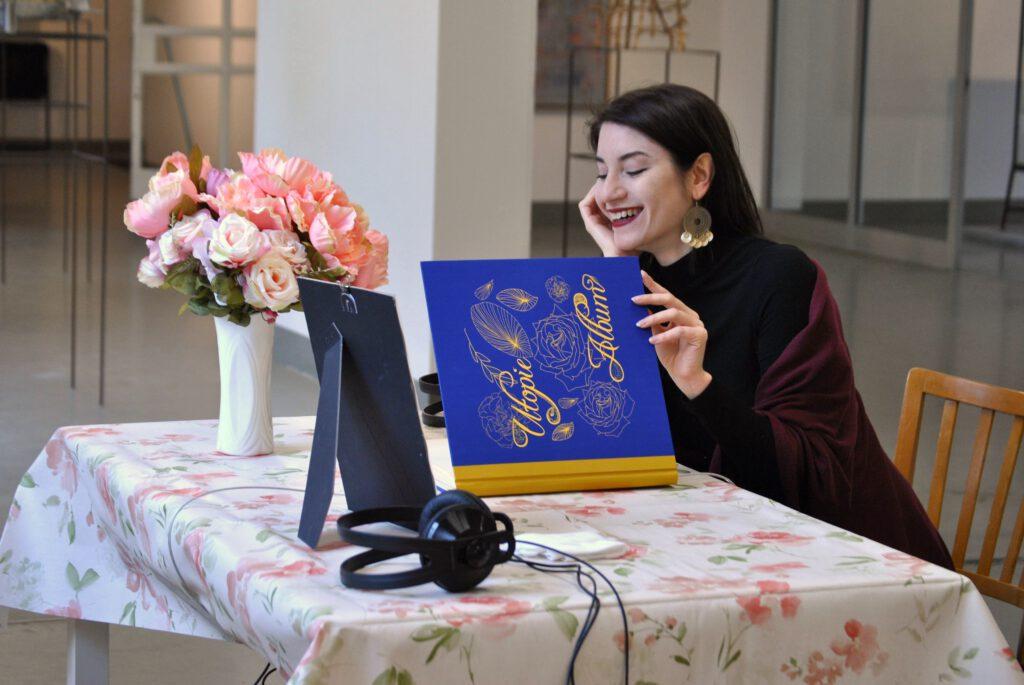 Auf dem Foto sitzt eine Frau an einem Tisch und blättert in einem Buch. Auf dem Titel steht Utopie Album. Die Frau lacht. Auf dem Tisch befinden sich ein Buch, Kopfhörer, ein Bilderrahmen und ein Blumenstrauß